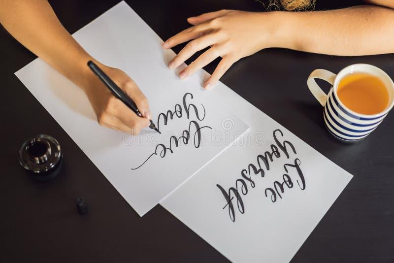Amour vous-m?me Le calligraphe Young Woman ?crit l'expression sur le livre blanc Inscrire les lettres d?cor?es ornementales image stock