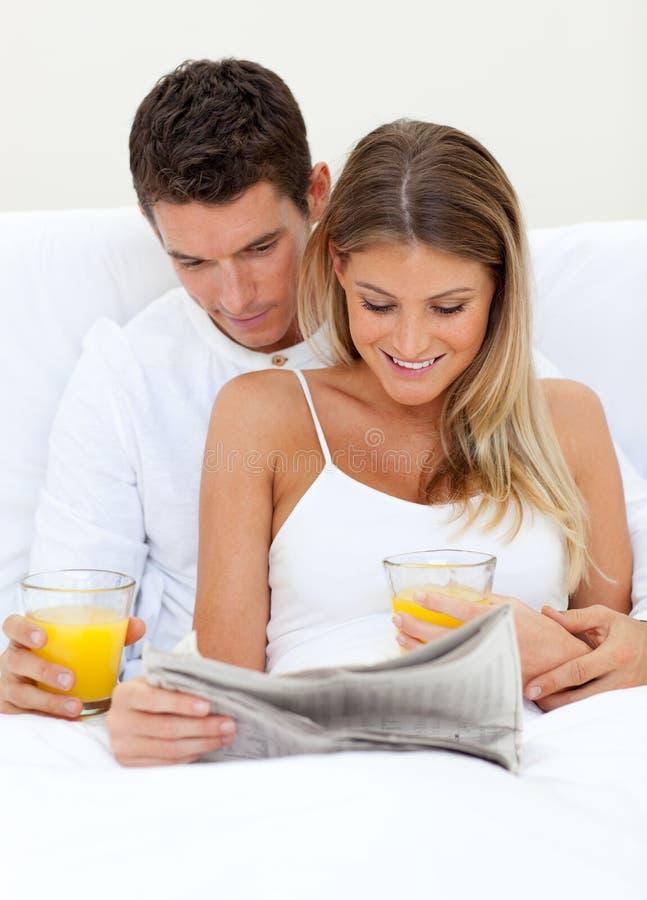 Amoureux affichant un journal et un boire image libre de droits