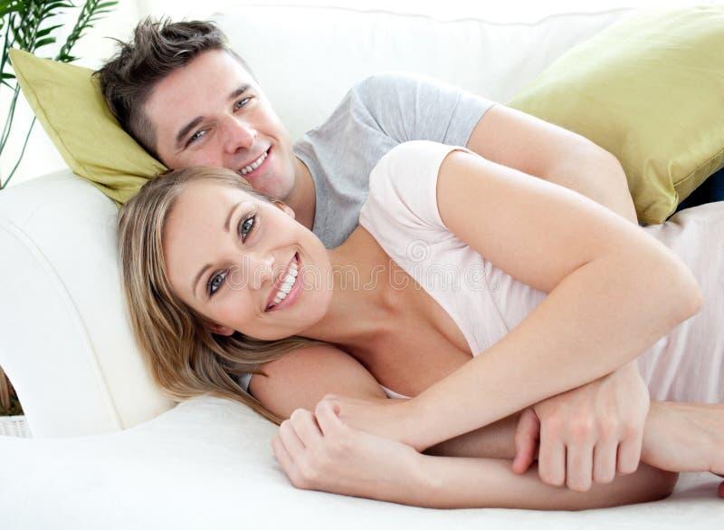 Amoureux de sourire ayant l'amusement ensemble sur un sofa images stock