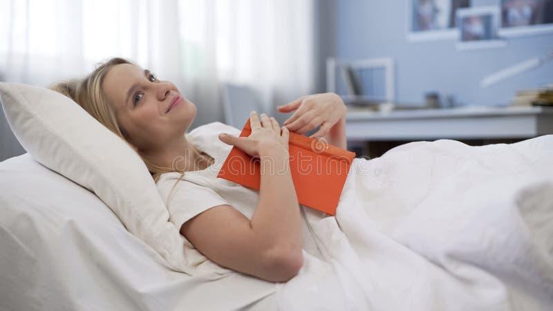 Amoureux des livres rêveur inspiré par le best-seller intéressant, se situant dans le lit, imagination image stock