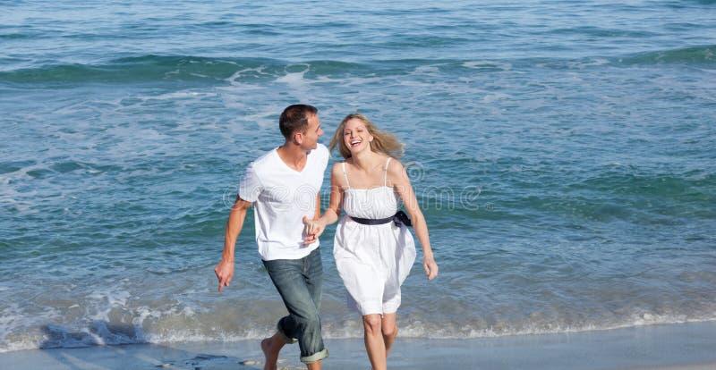 Amoureux heureux ayant l'amusement au bord de la mer images libres de droits