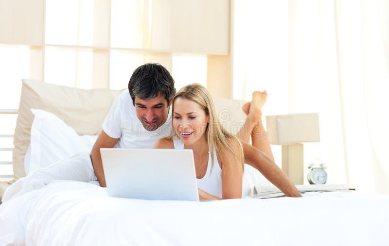 Amoureux joyeux à l'aide de l'ordinateur portatif se trouvant sur le bâti image libre de droits