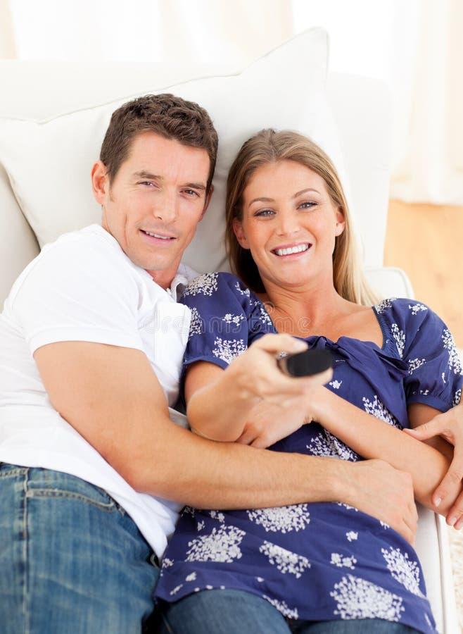 Amoureux Relaxed regardant la télévision se trouver sur le sofa photos stock