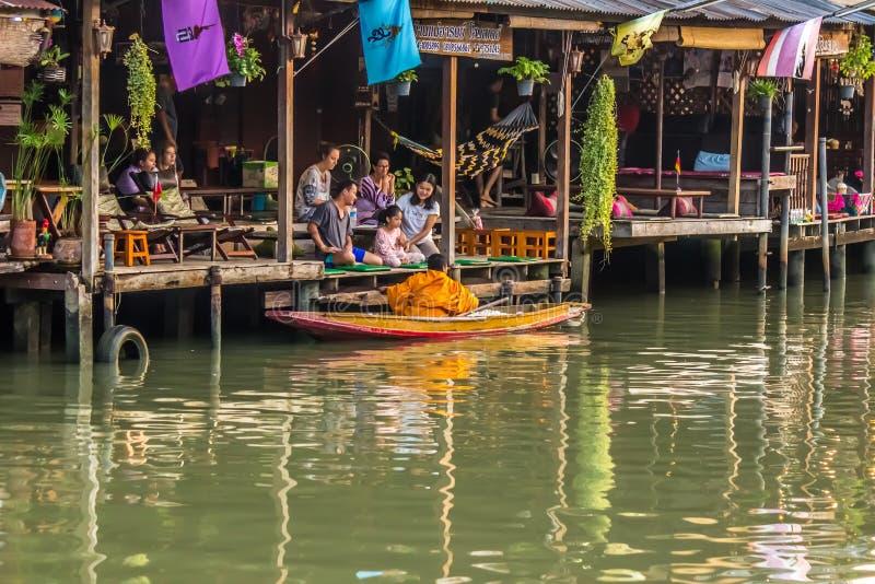 Amphawa浮动市场,夜功府,4月13,2019的泰国:和尚行接受食物奉献物的小船f 免版税库存图片