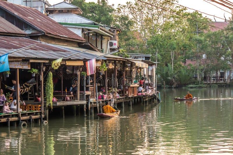 Amphawa浮动市场,夜功府,4月13,2019的泰国:和尚行接受食物奉献物的小船f 库存图片