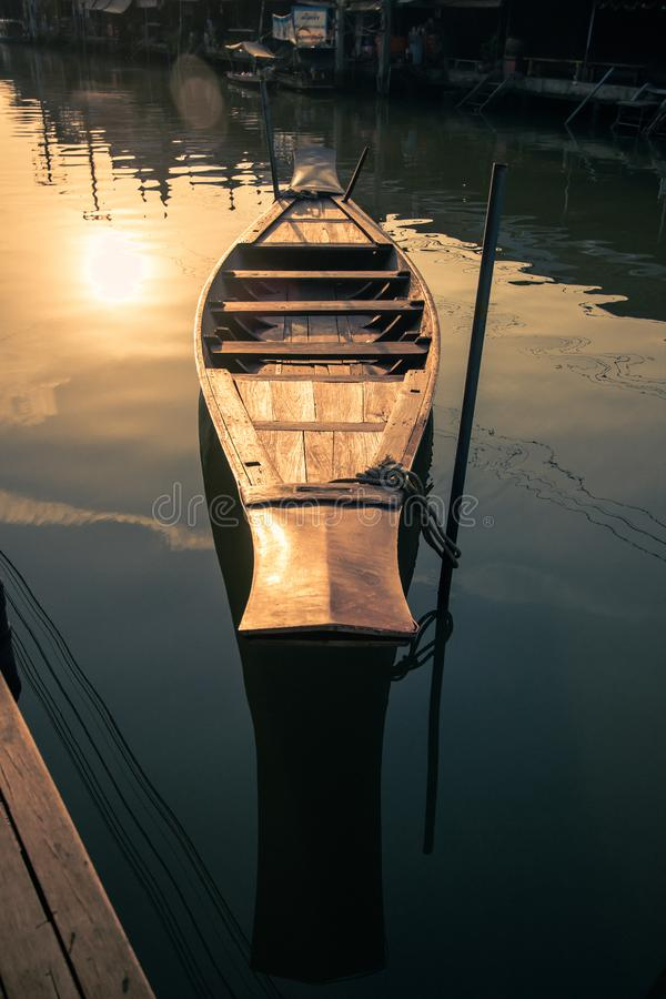 Amphawa Floating Market,Samut Songkhram Province,Thailand on April 13,2019:Vintage style wooden paddle boat and reflection shadow. Amphawa Floating Market is the royalty free stock photography