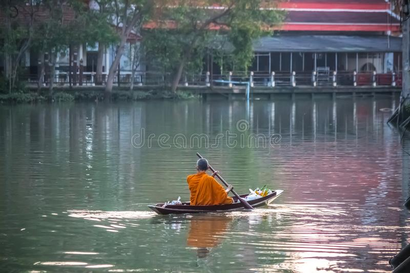 Amphawa Floating Market,Samut Songkhram Province,Thailand on April 13,2019:Buddhist monk rows the boat to receive food offerings f. Amphawa Floating Market is stock photography
