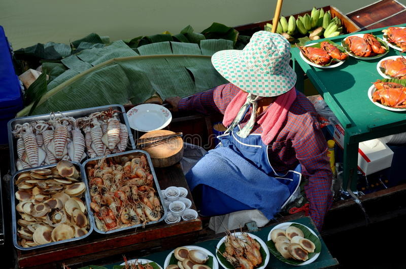 Amphawa, Thailand: Food Vendor at Floating Market. Woman wearing large hat to protect her from the sun sails along in her boat filled with seafood and fish which stock photography