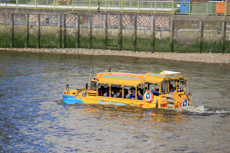 Amphibious craft on River Thames, London, England. An amphibious craft operated by London Duck Tours taking a load of tourists on a sighseeing tour of London royalty free stock photo