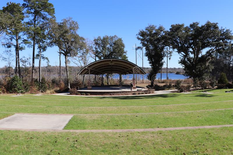 Amphitheater with green grass, blue sky, and water background royalty free stock photography