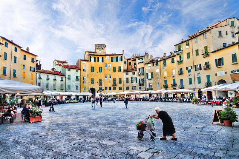 Amphitheatre Square in Lucca, Italy. Old lady with shopping cart trolley in Piazza dell`Anfiteatro from the city of Lucca, Italy stock photo
