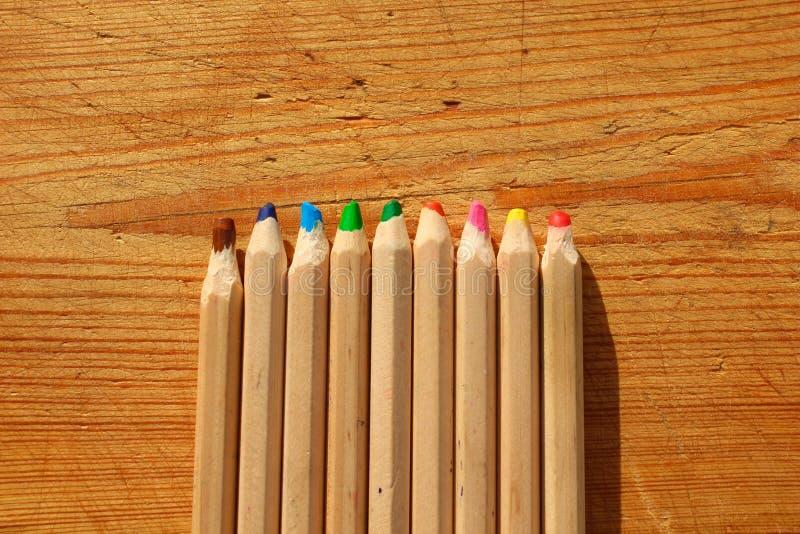 Ampie matite di legno multicolori su fondo di legno Vista superiore immagine stock