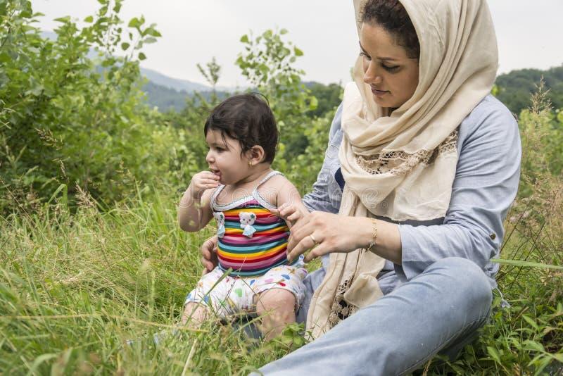 Ampio punto di vista della madre musulmana e piccolo del bambino che godono nella f all'aperto immagine stock libera da diritti