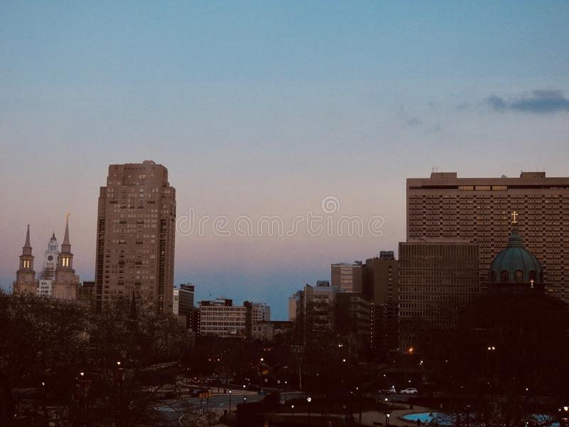 Amplia toma de edificios altos en una ciudad con luces bajo el cielo nublado en la noche fotografía de archivo