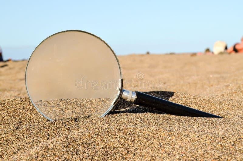 Amplie o vidro na praia da areia imagens de stock