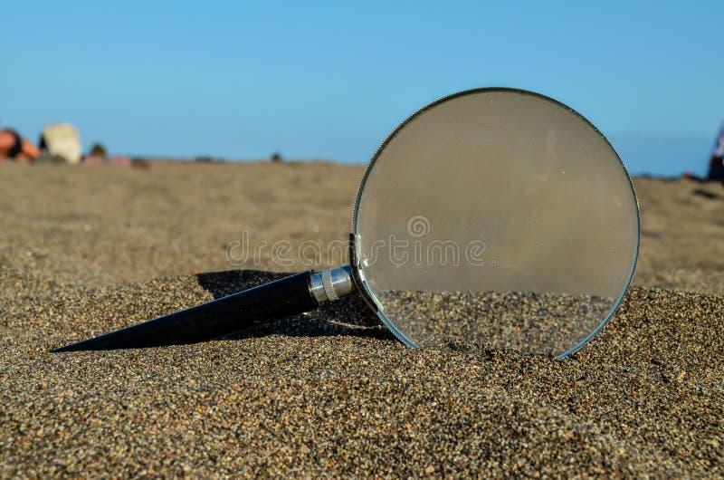 Amplie o vidro na praia da areia imagens de stock royalty free