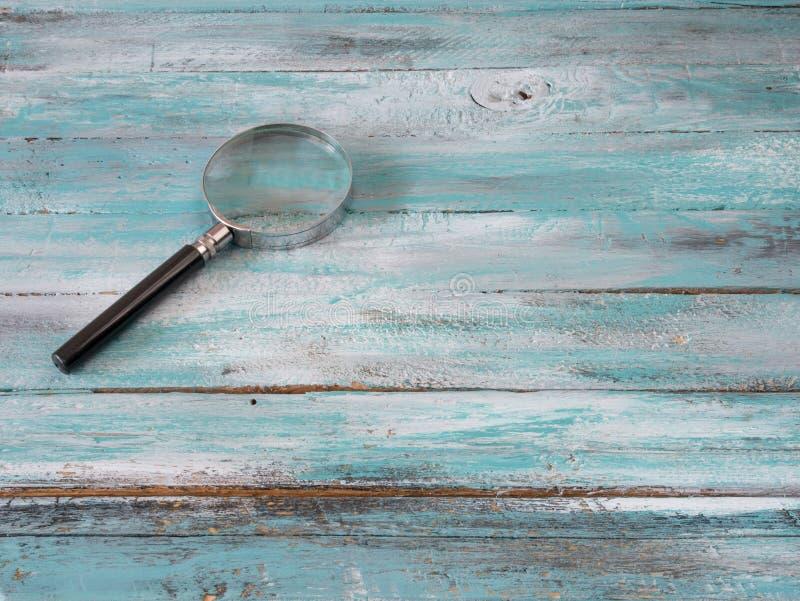Amplie o vidro no fundo azul Foto do conceito imagem de stock