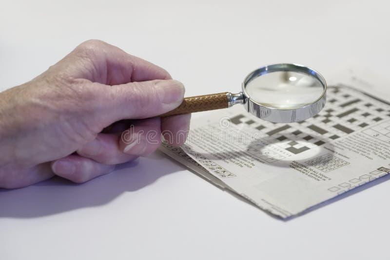 Amplie o vidro usado pela pessoa pobre superior idosa idosa da vista e da visão para palavras cruzadas fotografia de stock