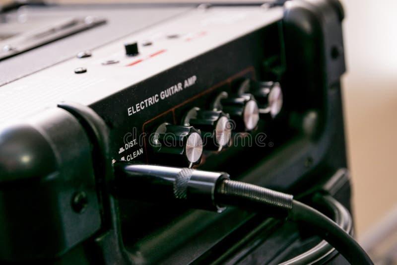 Amplificateur de guitare avec des cadrans et des contrôles pour le volume, gain, basse, triple Le câble de Jack s'est relié photos stock