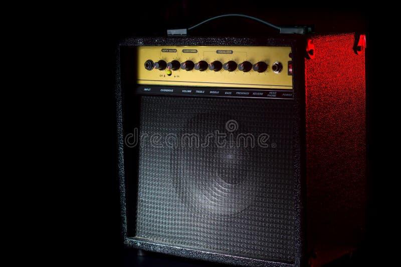 Amplificatore nero della chitarra su un fondo nero con un flash rosso immagini stock libere da diritti