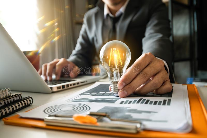 Ampola com a mão do negócio que trabalha com laptop a fotografia de stock royalty free