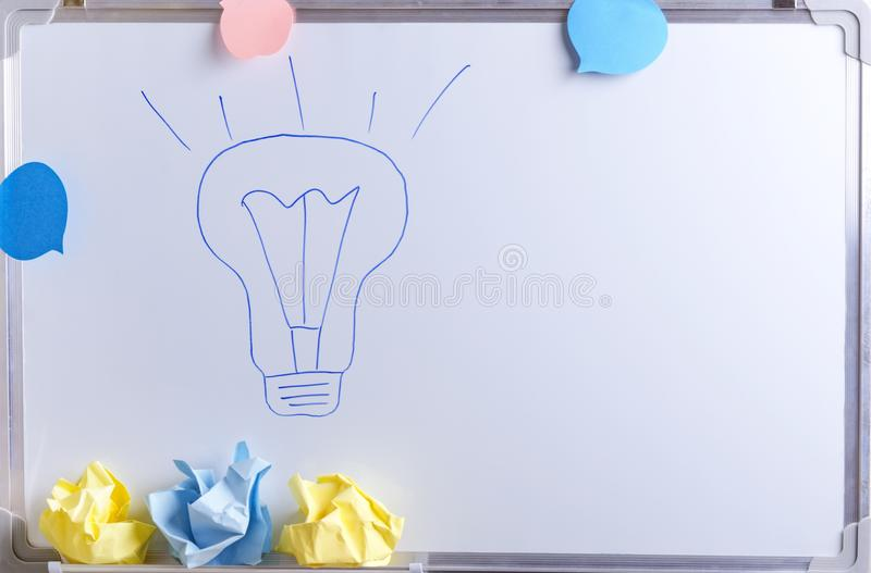Ampola do desenho da mão e papel amarrotado na placa branca do escritório como um símbolo de criativo e do pensamento sobre ideia fotos de stock