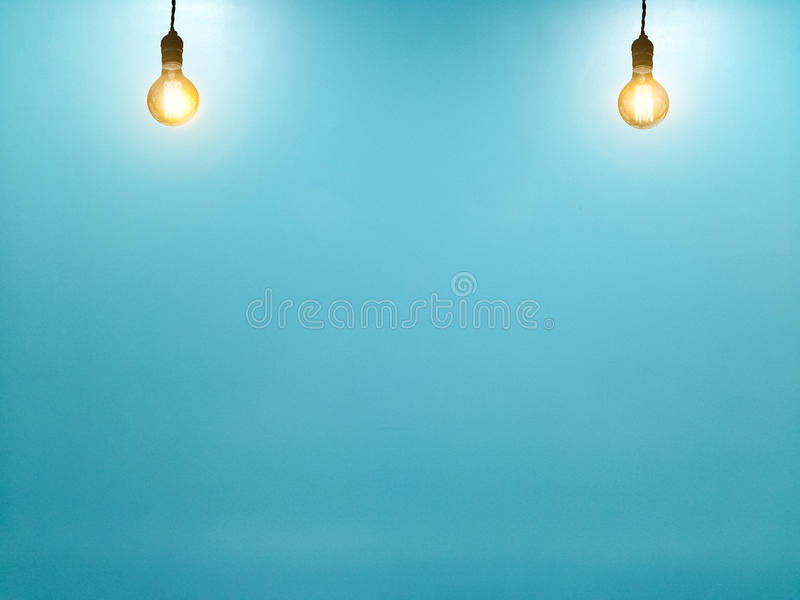 Ampola do tungstênio no fundo azul vazio da parede foto de stock royalty free