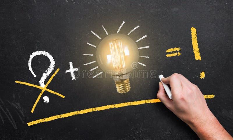 Ampola em um quadro-negro e em uma mão com o giz que faz uma equação do sucesso imagem de stock