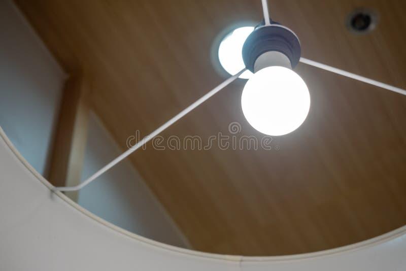Ampola na lâmpada que pendura do teto no fundo borrado foto de stock