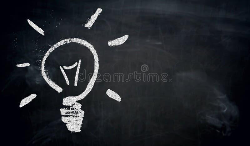 Ampola pintada com giz no conceito do quadro-negro imagens de stock royalty free
