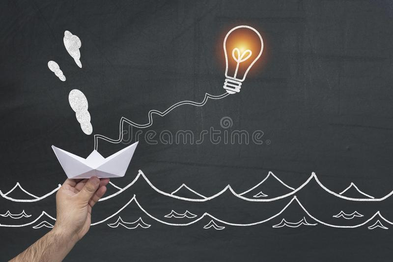 Ampola que faz movimento o barco de papel como uma metáfora do sucesso para a resolução de pensamento esperta desafios a econômic imagem de stock royalty free