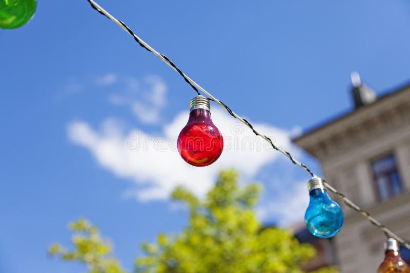 Ampola vermelha em um fio com outras lâmpadas foto de stock