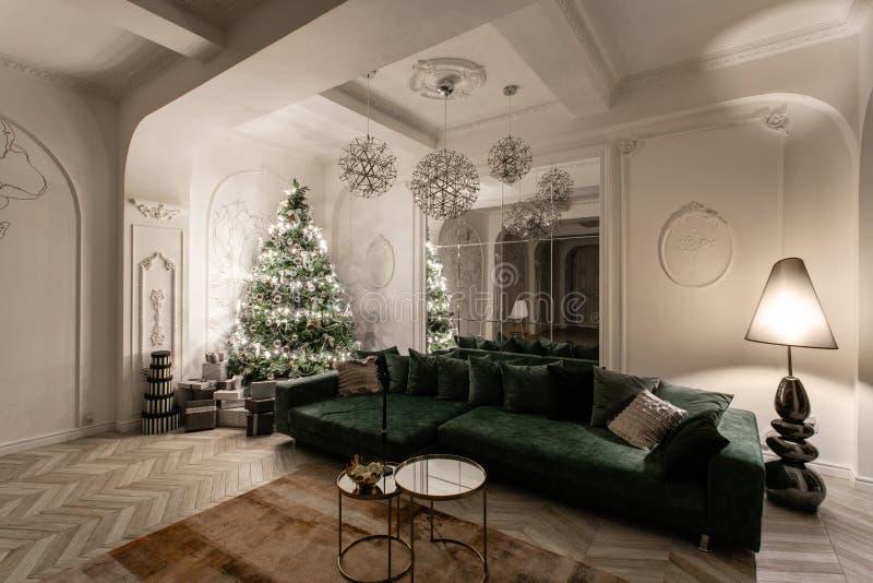 Ampolas da festão Noite do Natal apartamentos luxuosos clássicos com a árvore de Natal decorada Salão de vida grande fotos de stock