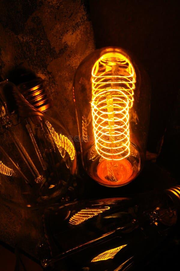 Ampolas incandescentes clássicas Cobbled de Edison com fios de incandescência visíveis na noite fotos de stock