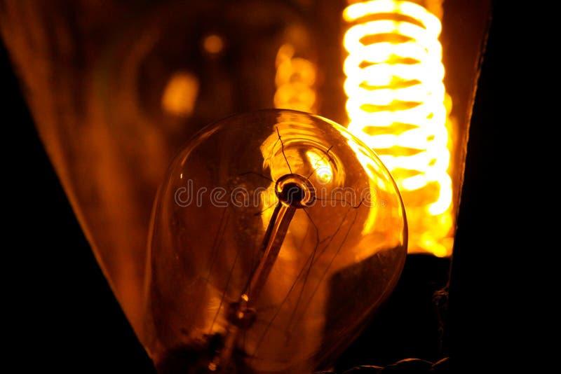 Ampolas incandescentes clássicas Cobbled de Edison com fios de incandescência visíveis na noite foto de stock