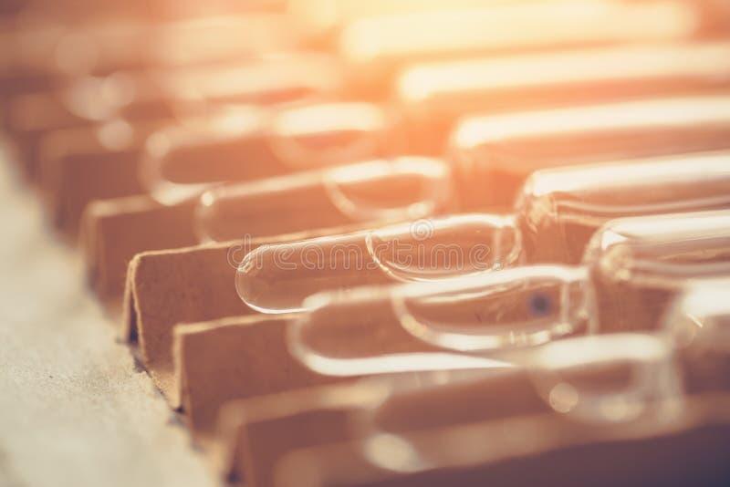 Ampolas ou tubos de ensaio ou ampola médica com medicina em uma caixa com efeito da luz solar foto de stock royalty free