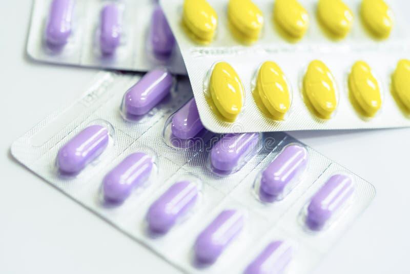 Ampollas amarillas y púrpuras de píldoras en el fondo blanco imagenes de archivo