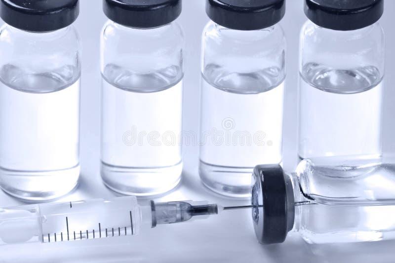 Ampollas médicas con la vacuna y la jeringuilla en el fondo blanco foto de archivo libre de regalías