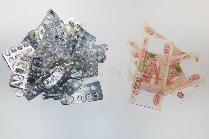 Ampollas vacías de píldoras y muchas cuentas de la rublo en un fondo blanco El concepto de alto coste de drogas fotos de archivo libres de regalías