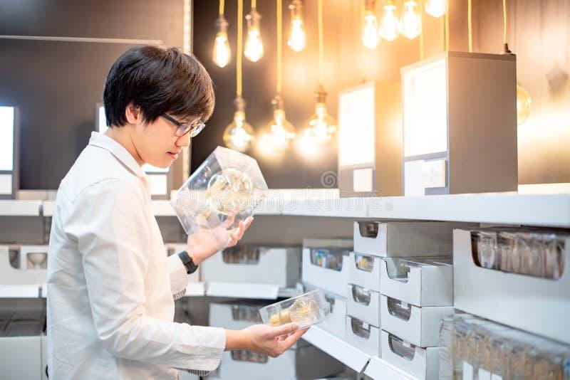 Ampoule électrique de achat de jeune homme asiatique photo libre de droits