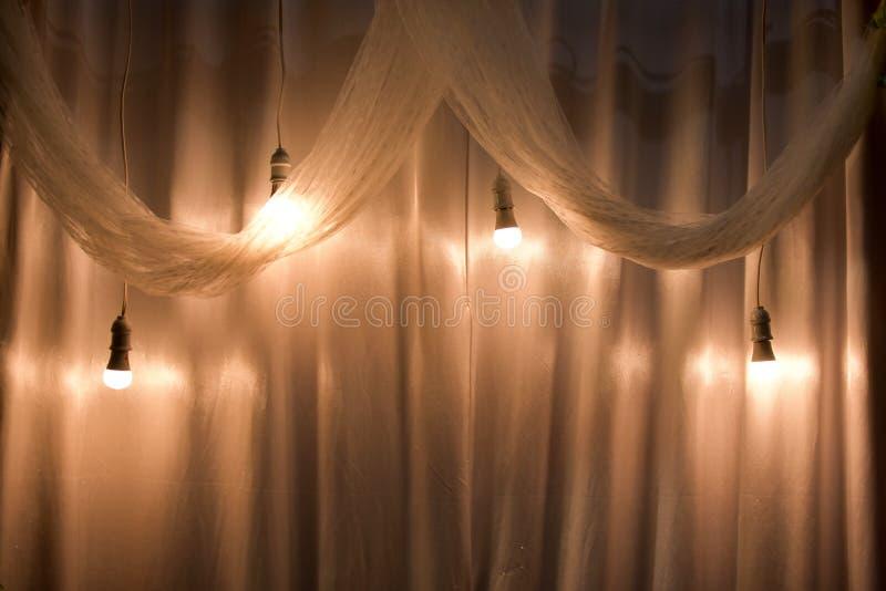 Ampoule avec la lumière jaune et le tissu blanc comme décoration l'épousant de pièce photos stock