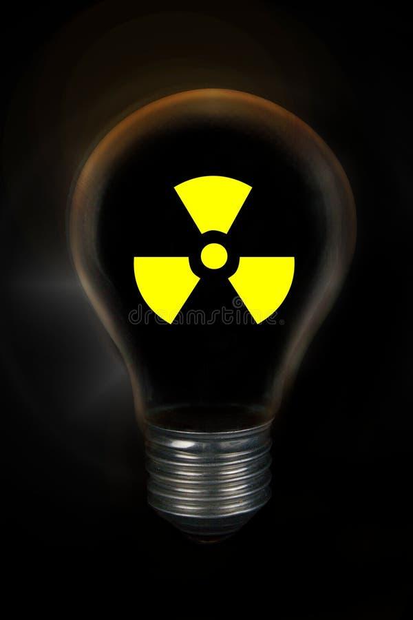 Ampoule avec le symbole nucléaire radioactif devant le fond noir photo libre de droits