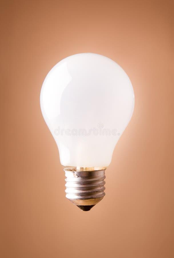 Ampoule brillante d'isolement sur le fond beige images stock