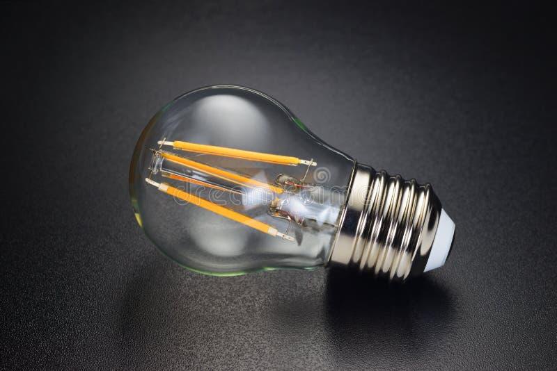 Ampoule de filament de LED sur le noir image stock