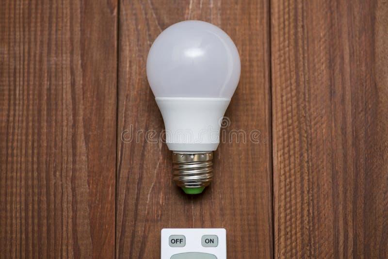 Ampoule de LED et à télécommande avec des boutons en marche et en arrêt sur un fond en bois photographie stock