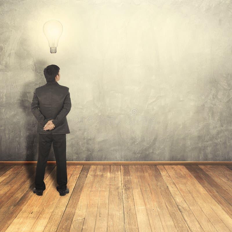 Ampoule de pensée d'idée d'homme d'affaires et mur vide pour le texte et le fond photographie stock