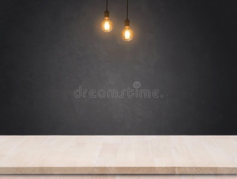 Ampoule de tungstène avec le fond de mur de ciment et la table noirs en bois photo stock