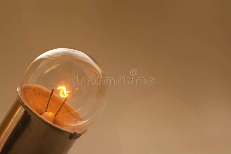 Ampoule rougeoyante sur le fond de brun d'or Rétro lampe de style avec la surface et l'élément sphériques idéaux de filament Macr images stock