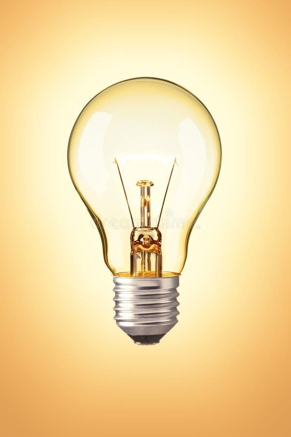 Ampoule sur le fond orange photos libres de droits