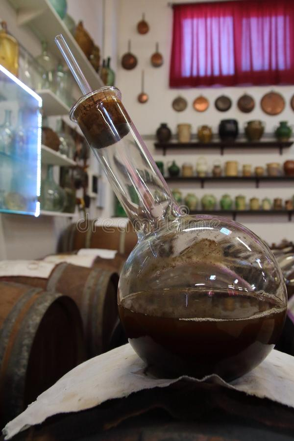 Ampoule of very old Balsamico on an old cask containing balsamico. Ampoule containing very old Balsamic Vinegar of Modena, following ancient recipe stock photo